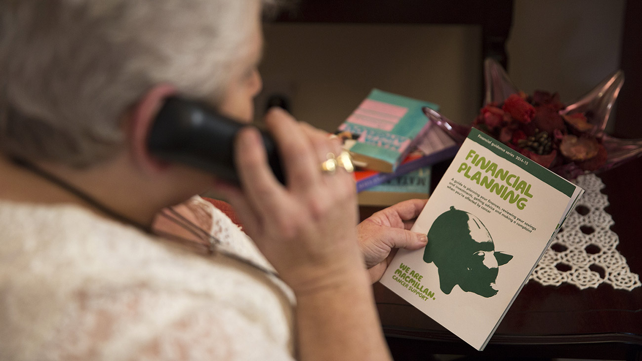Philomena on the phone to the Macmillan Support Line. In her hands she holds a Macmillan leaflet about finances.