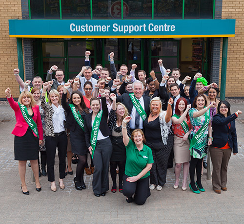 A large group of people stand cheering in front of a building with the sign 'Customer Support Centre'