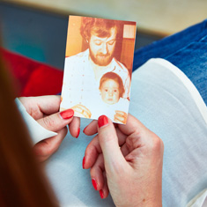 Vikki is holding a faded photo which shows her as a baby, sitting in her father's lap. Her father is looking down at her proudly.
