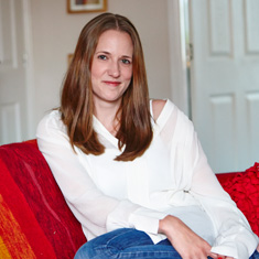 Vikki today, a woman in her late 20s with long brown hair and wearing a V-necked white blouse.
