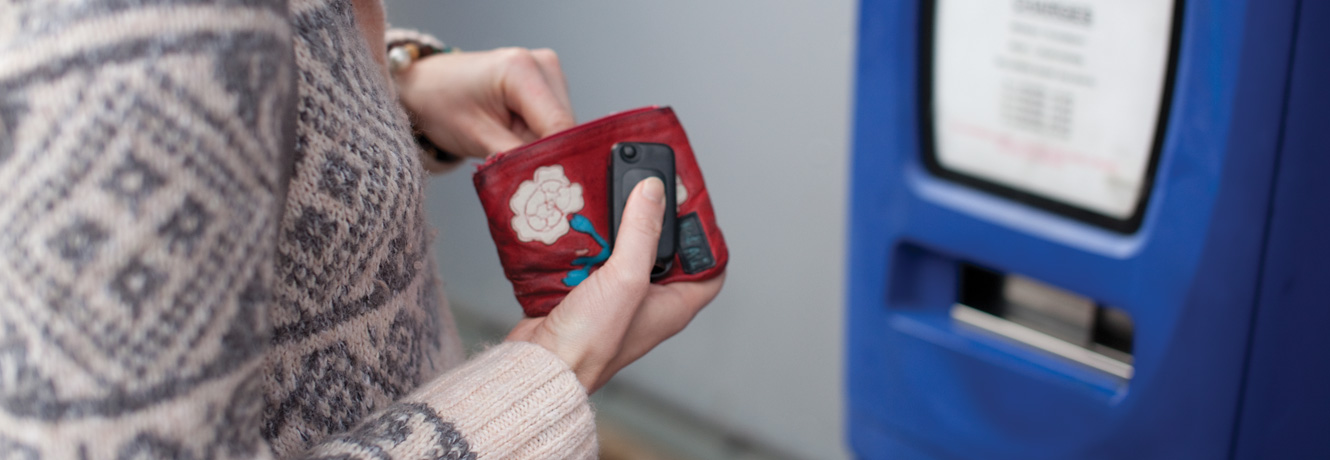 A woman finds change in her purse for a hospital car parking meter.