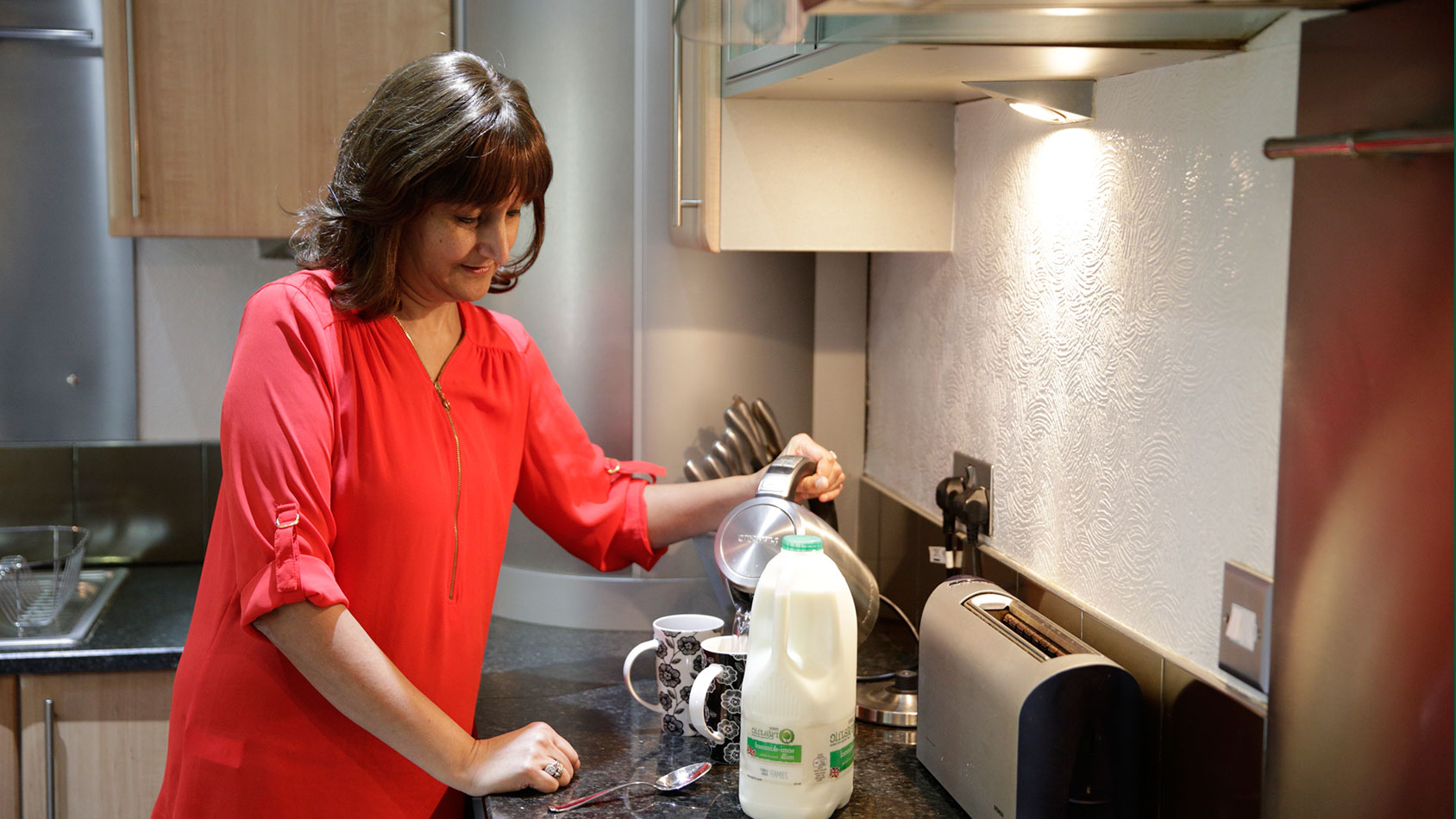 Ravinder makes a cup of tea in her kitchen.