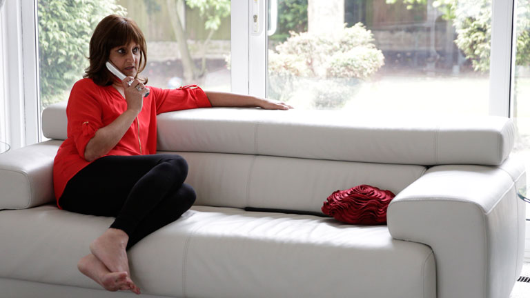 Ravinder sits on a white sofa with the phone to her ear. She appears to be in her living room.