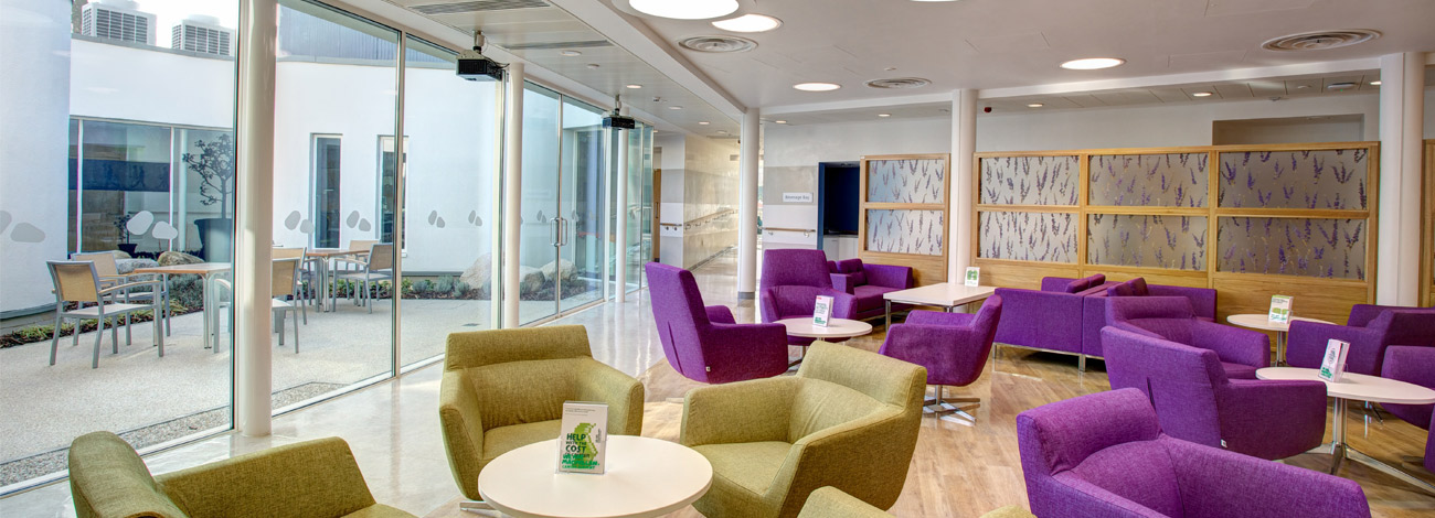 The interior of the Sir Robert Ogden Macmillan Centre in Harrogate there are green and purple comfortable chairs and big glass doors opening onto a garden area.