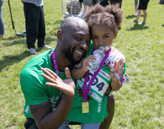 A man squatting down with his arm around his daughter, both with medals around their neck and wearing green Macmillan running T-Shirts