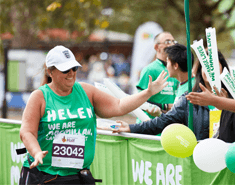 A woman 'Helen' wearing a green Macmillan running t-shirt high fiving a supporter as she runs