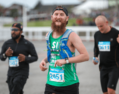 A man with a big ginger beard running and wearing a green Macmillan vest, a back to front black cap and a blur running drinks vest