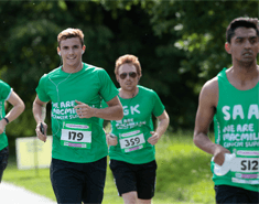 Group of three young men running, all wearing green Macmillan t-shirts or vests