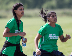 Two young women wearing green Macmillan T-shirts running, one holding a bottle of water