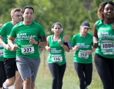 Group of six mean and women spread across the road, running and all wearing green Macmillan running vests or T-shirts