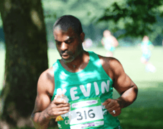 A man with big arms wearing a green Macmillan running vest that has 'Kevin' written across it.