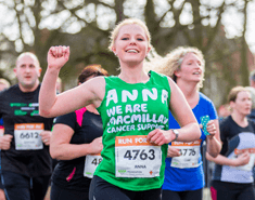 A young blonde woman punching the air wearing a green Macmillan running vest with Anna written on the front of it and other runners behind her.