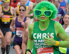 Man painted green, with comedy green wig, sunglasses and wearing a green Macmillan vest