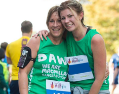 Two young women wearing green Macmillan shirts smiling with their arms around eachother.