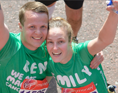 A man and a woman wearing green Macmillan shirts smiling with their arms in the air