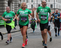 Macmillan runners in green t-shirts running through a city
