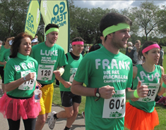 Macmillan runners wearing green t-shirts running through a park