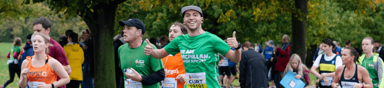 Man running and looking at the camera giving two thumbs up, wearing a cap and green Macmillan t-shirt surrounded by other runners.