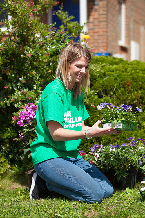 A blonde woman in a Macmillan t-shirt kneels while gardening