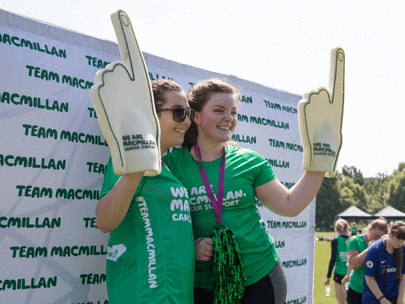 Two young women wearing green Macmillan t-shirts with posing together with foam fingers