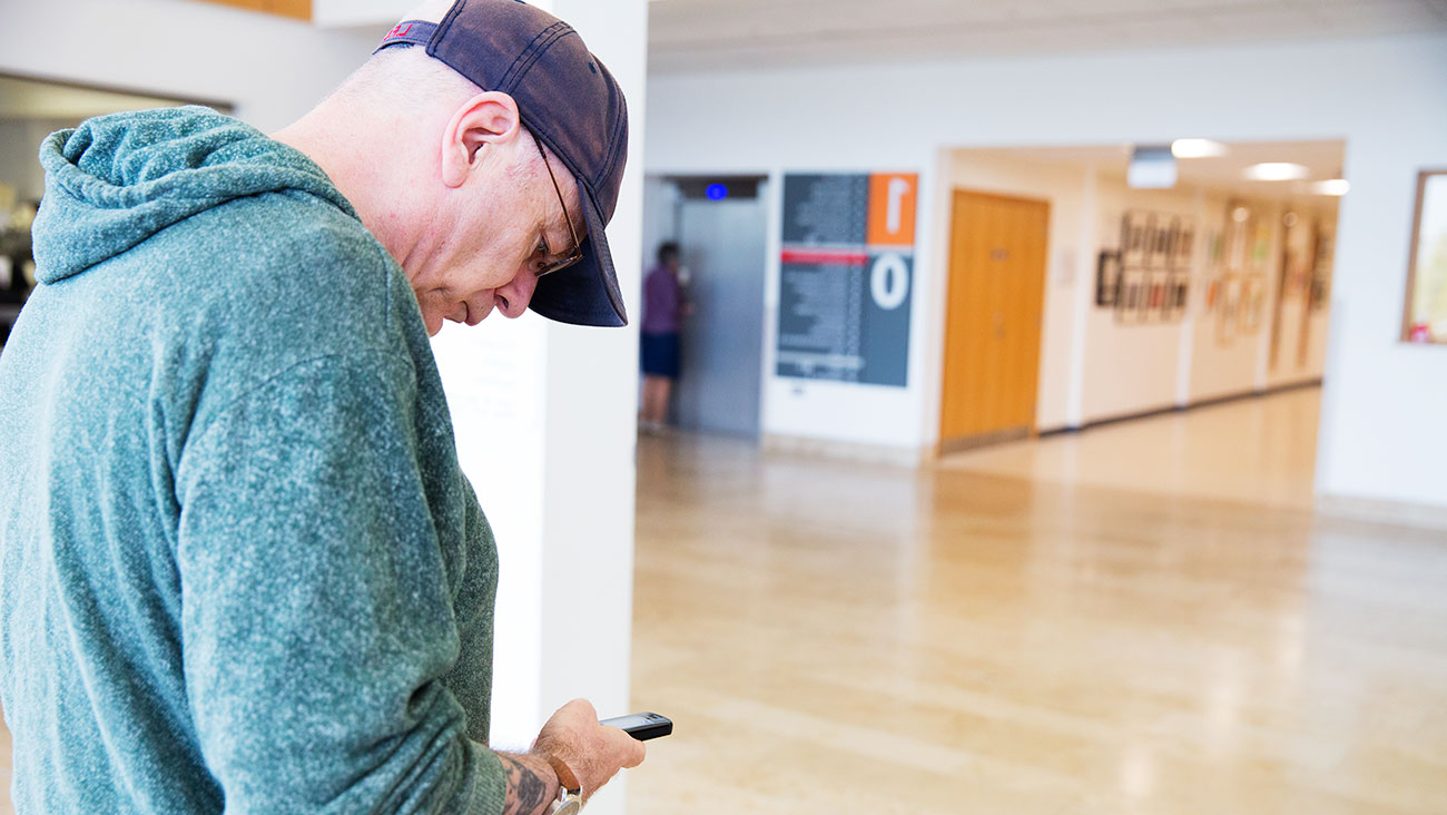 Gary walking through the hospital using his phone