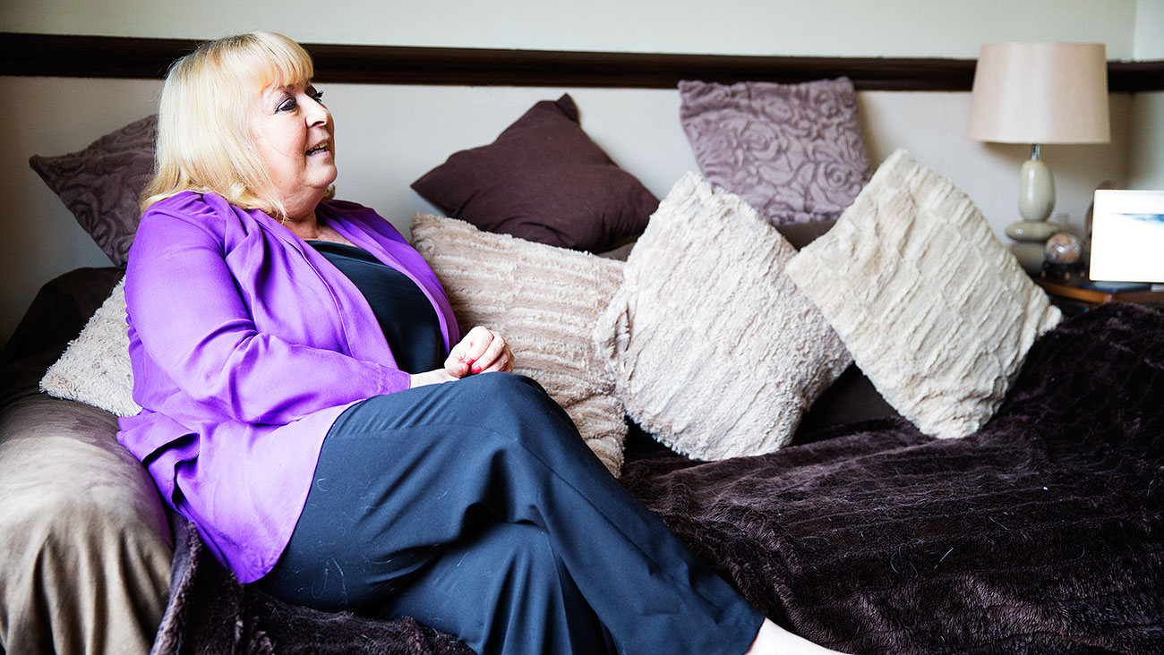 Patsy sits on her purple sofa