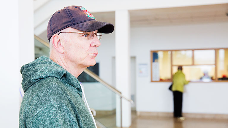Gary in hospital wearing his baseball cap and glasses