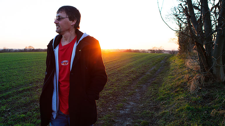 Paul on a walk in a field with the sun setting in the background