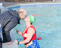 Woman in a swimming pool kissing a man on the edge of the pool. She is wearing a wonderwoman swimsuit and a green Macmillan swimming hat.
