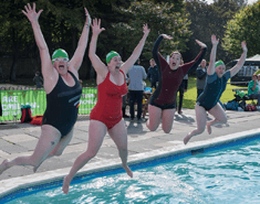 Four women doing star jumps into a swimming pool.
