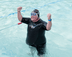 Man wearing a black swimming hat and westuit standing up in a pool with both arms up in celebration.
