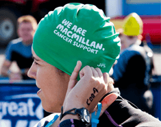 Close up of the side of a woman's face, wearing a green Macmillan swimming cap.