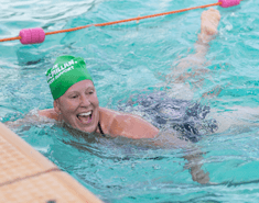 Woman smiling as she swims to the edge of the pool, wearing a green Macmillan swimming cap.