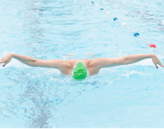 Front on shot of someone wearing a green Macmillan swimming hat in the middle of a butterfly stroke.