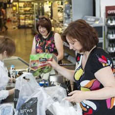 Sharon helps her mum pack the shopping at a supermarket