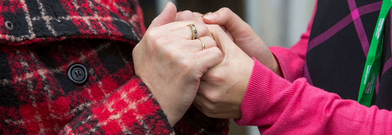 A close-up of the hands of two women, clasped together in support.