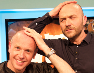 Two bald men touching their heads.