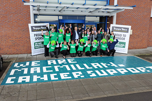A group of Topps Tiles employees stand outside a store with We are Macmillan Cancer support written in tiles on front of the group.