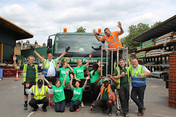 A group of Travis Perkins' staff and Macmillan employees stand in front of a Travis Perkins lorry.
