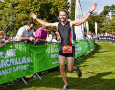 Man wearing a triathlon suit with arms in the air as he runs past barrier with Macmillan banners.