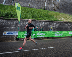 Woman running downhill past Windsor Castle and Macmillan support banners.