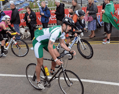 Three people cycling up a steep hill with supporters on the side of the road. Cyclist in the foreground is wearing a green Macmillan triathlon suit.