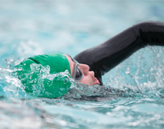Person swimming front crawl, breathing to the side, wearing a wetsuit, goggles and green Macmillan swimming hat.