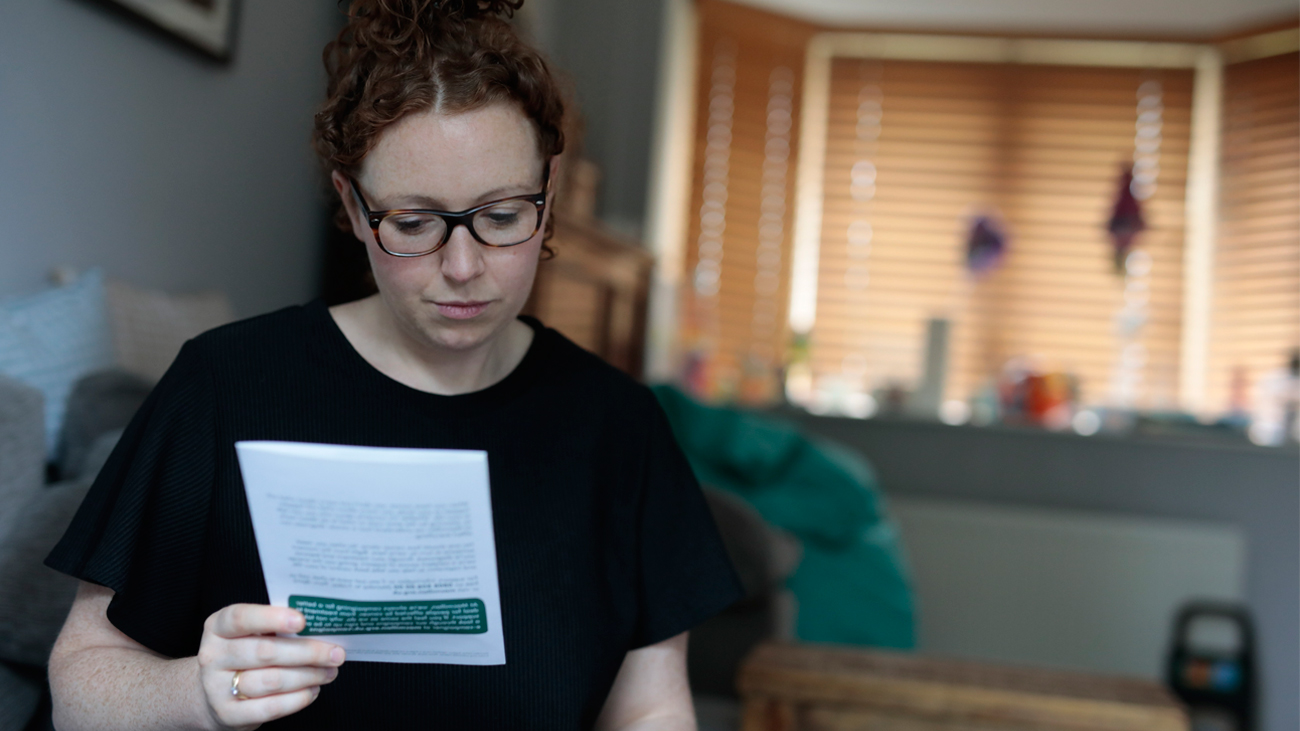 A photograph of Laura reading a money worries leaflet.