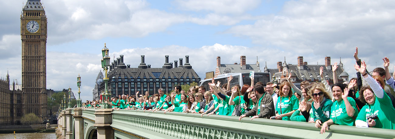 Macmillan staff lined up waving on Westminster bridge. Big Ben is in view.