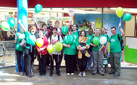 A large group of Wilko employees stand outside a store holding balloons and cheering.