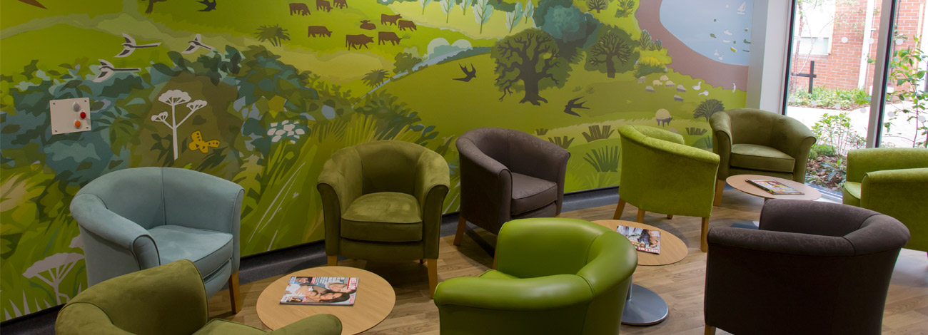 Inside the Woolverstone Macmillan Centre in Ipswich there's a countryside mural and green and brown armchairs with low tables.