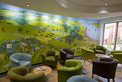 Inside the Woolverston Macmillan Centre in Ipswich there's a countryside mural and green and brown armchairs with low tables.