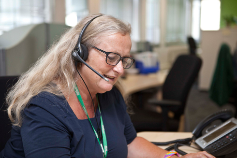 A middle aged woman with long blonde hair and glasses, wearing a telephone headset and talking to someone on the end of a phone.