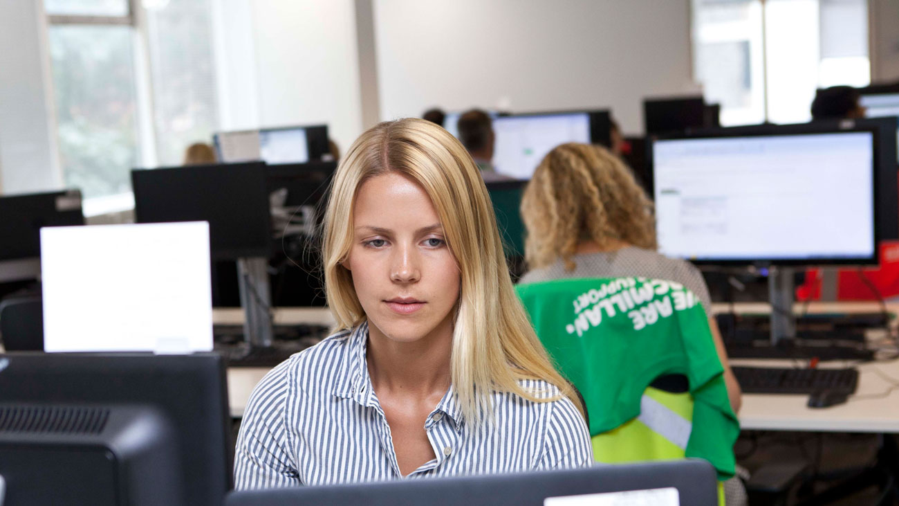 A Macmillan intern sits at a desk in an office.
